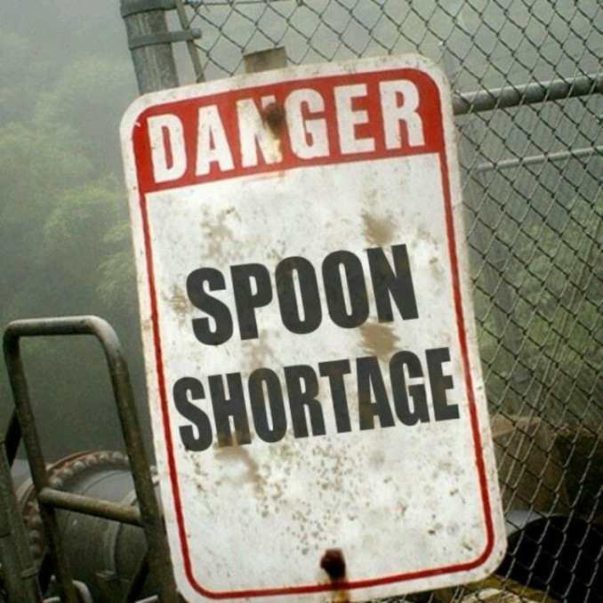 """beaten up sign next to a fence and chair that both look battered. The sign says """"Danger SPOON Shortage"""""""