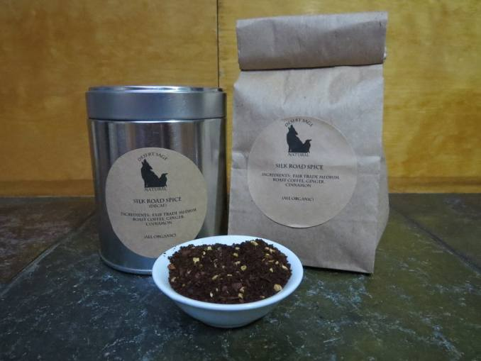 """A small white bowl full of a blend of coffee, cinnamon, and ginger. Behind it stand a bag and a tin. The labels read """"Silk Road Spice, Ingredients: Fair Trade medium Roast Coffee, Cinnamon, and Ginger (All Organic)"""" One is marked as caffeinated, the other as decaf."""