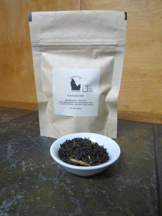 "A zip-seal bag with a label indication it is ""Watson's Wit"" where the ingredients are listed as a series of organic black tea. In front of the bag is a small white bowl, filled with that blend of black teas."