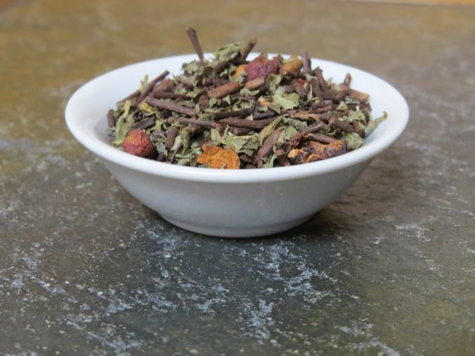 A small white bowl on a textured green marble table full of a blend of roasted kukicha, hawthorn berries, and lemon balm.