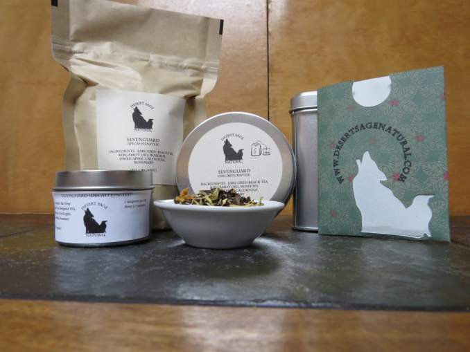 "A small white bowl set on a textured green marble tabletop, the light catching the tea tin just behind so the bowl has a halo of light.  The bowl is full of a mix of flowers, fruit, and tea.  To the left of the bowl is a small tea tin, to the right a rectangular packet with the Desert Sage Natural Raven and Coyote logo as a cutout and www.desertsagenatural.com ringing the coyote's head.  A bit further back behind is a large bag of tea.  The labels read:  ""Elvenguard (Decaffeinated), Ingredients:  Earl Grey, Rosehips, Calendula, Dried Apple, Rosemary, (All Organic)"""