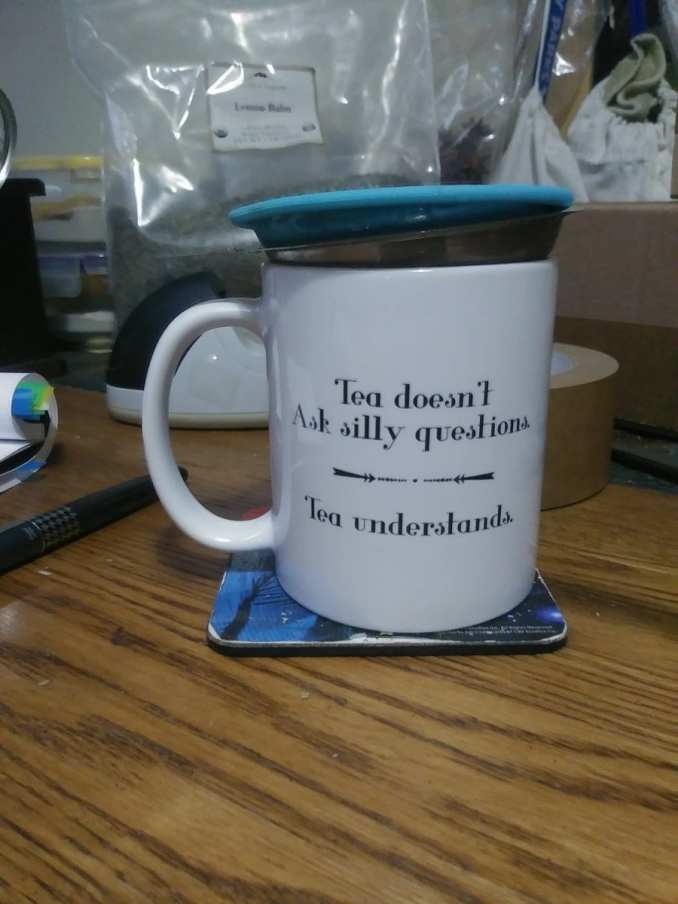 """A white tea mug with the words: """"Tea doesn't ask silly questions, tea understands,  In it is a tea strainer with a blue lid.  There is a grey pilot fountain pen to the left, a large bag of lemon balm behind, and there is a part of a roll of packing tape behind the mug, too."""