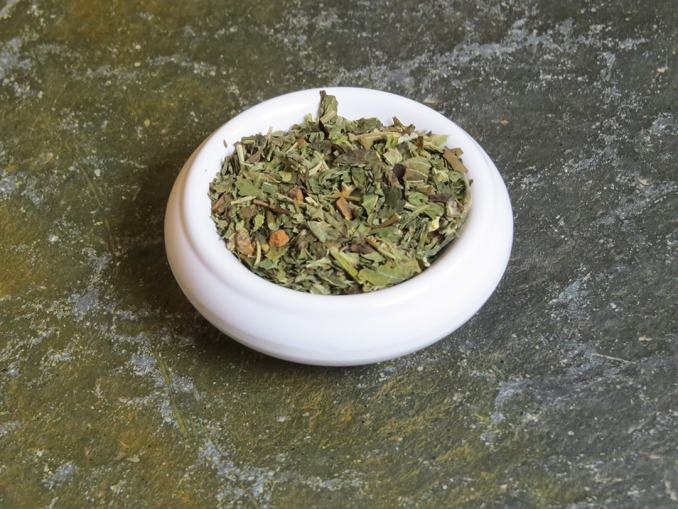 Small white bowl on a green textured stone table, filled with a blend of rosemary, chai, lemon balm, and chai spices.