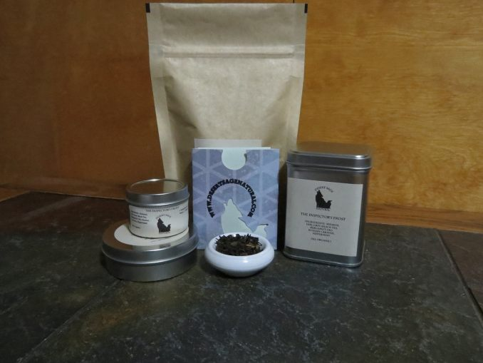 "A bag of tea, a tall tin of tea, and two round tins of tea, one large, one small, arrayed around a small white bowl full of a mix of teas and peppermint.  The labels read ""The Inspector's Frost.'"