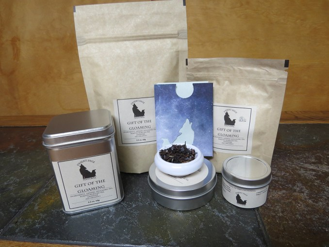 """An array of bags and tins of tea, a small rectangular packet with the Desert Sage Natural logo cut-out, and a small bowl of tea.  The labels read """"Gift of the Gloaming."""""""