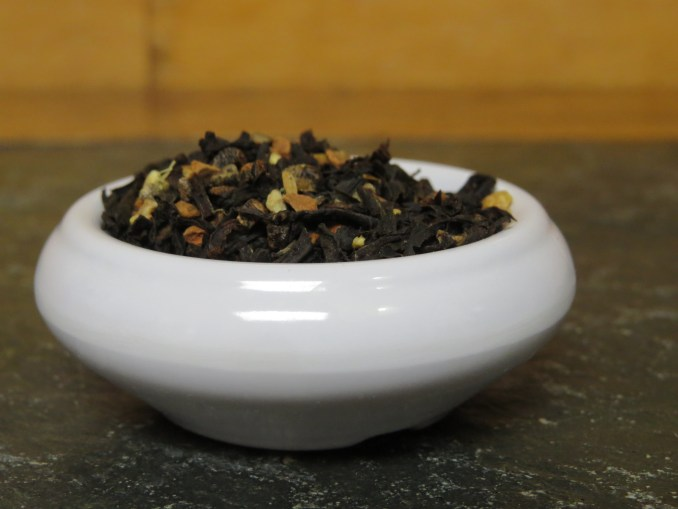 A small white bowl filled with a blend of black tea and chai spices.