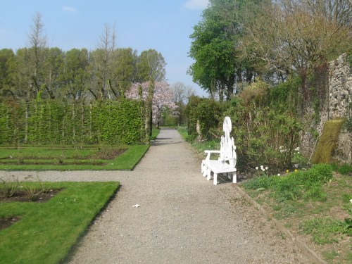 White garden bench by wall in the formal rose garden at Birr Castle Gardens