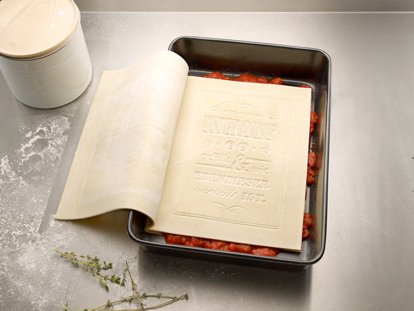 Book made of pasta in pan with first layer of lasagna ingredients