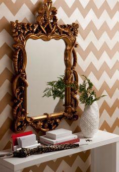 Papel de parede em chevron e espelho emoldurado no ambiente