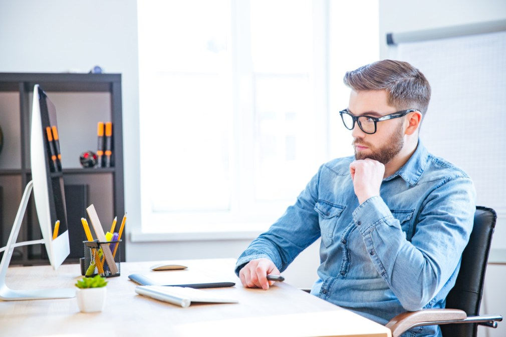 Thoughtful handsome young designer with beard in glasses using graphic tablet and computer and thinking