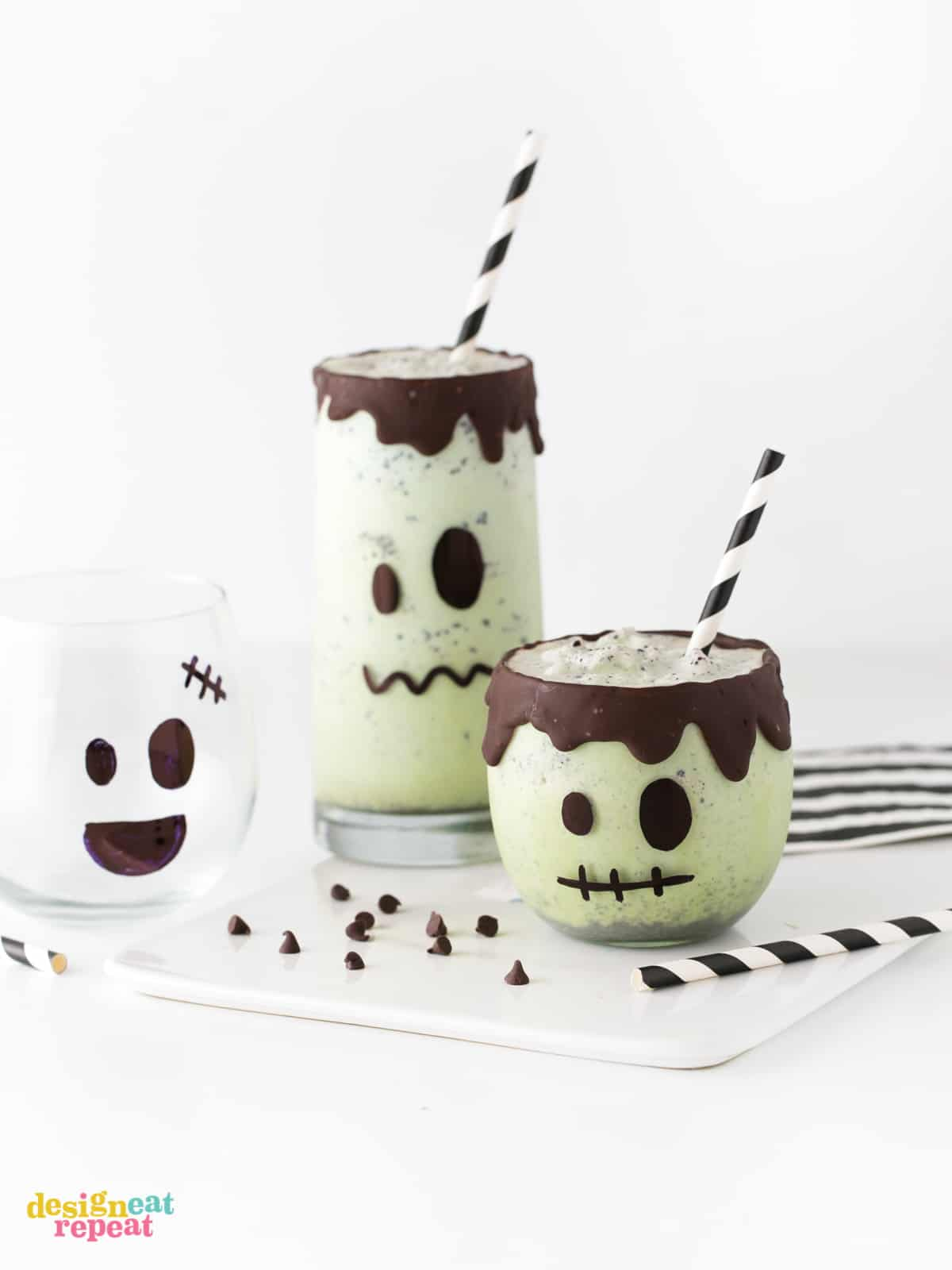 Mint chip green Halloween milkshakes decorated like Frankenstein with chocolate drip rim and striped black paper straws