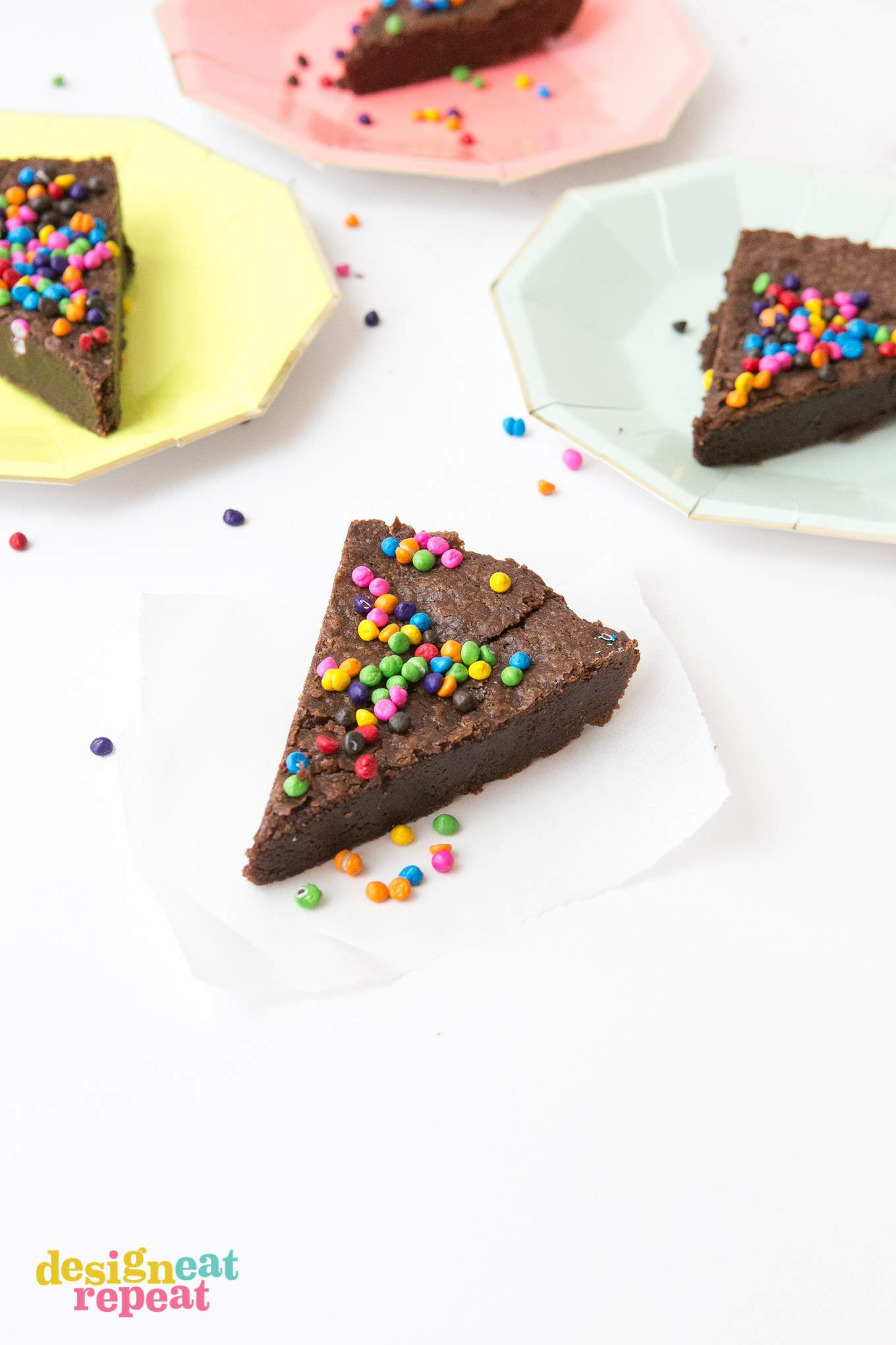 Slice of brownie pie with rainbow chips on piece of parchment paper and rainbow plates.