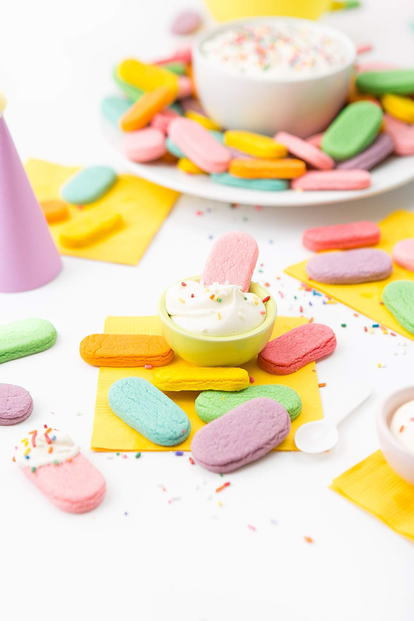 Pink sugar cookie being dipped in small bowl of frosting.