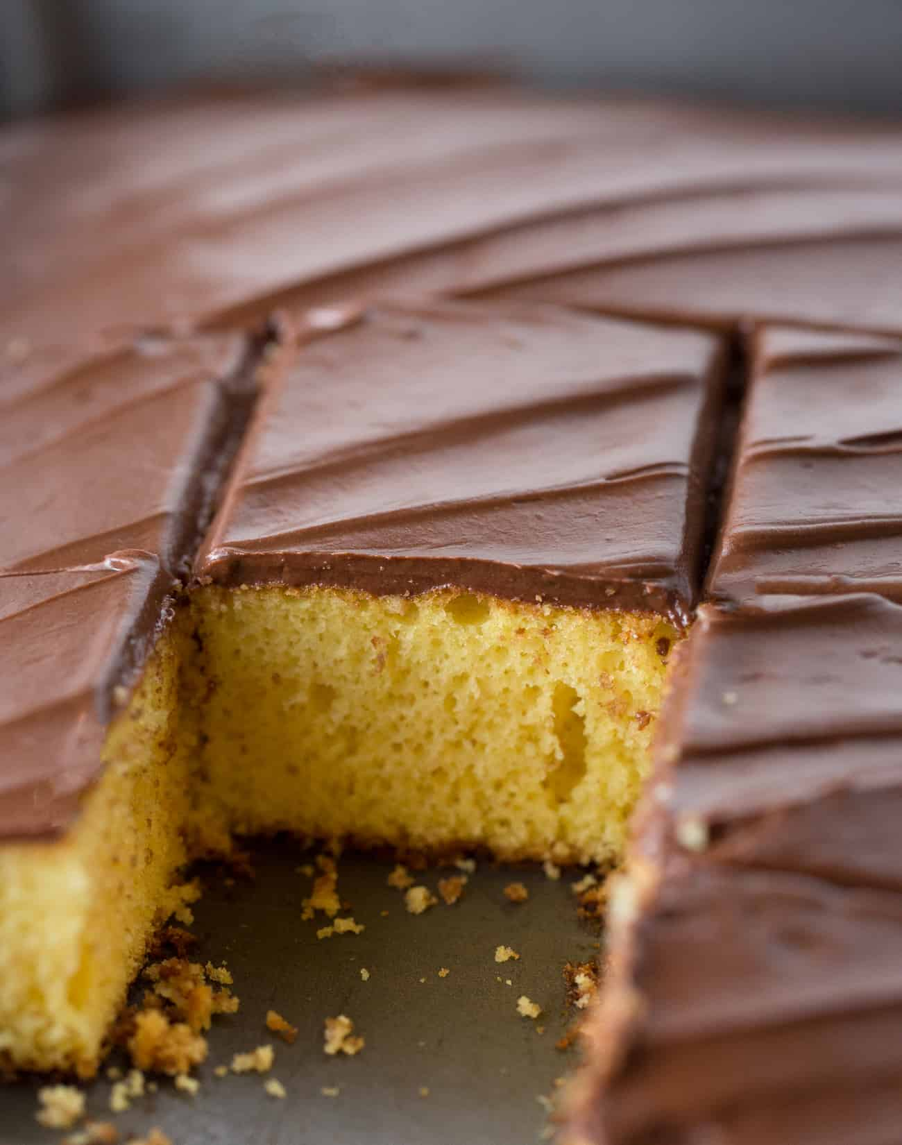 Close up shot of yellow cake square with easy chocolate frosting.
