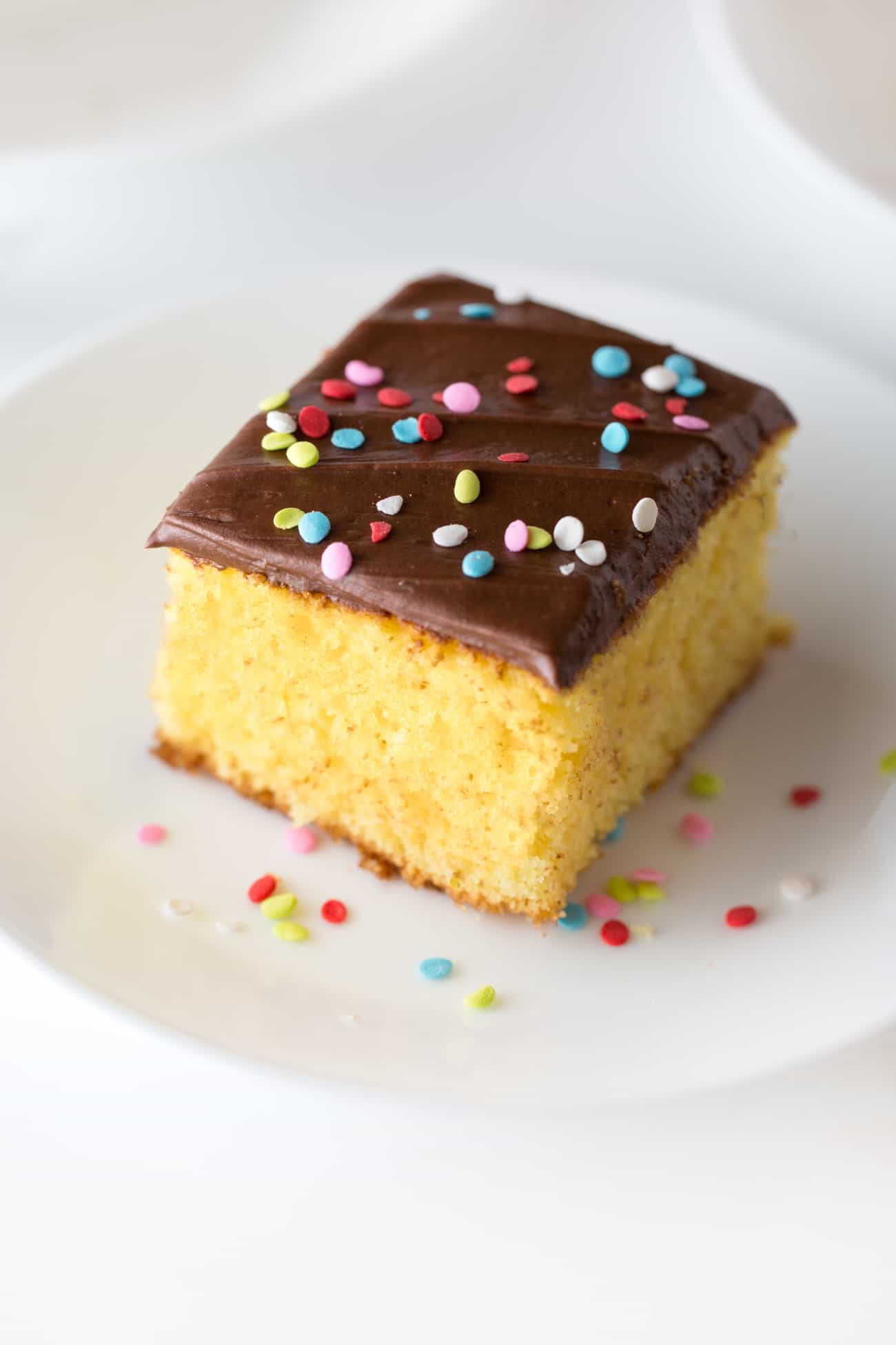 Square slice of yellow cake with easy chocolate frosting with rainbow sprinkle quins on top. On small white plate.