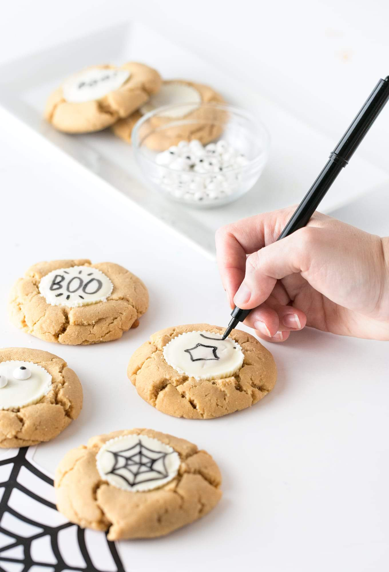 "Forget the fancy decorating and grab the edible food pen to draw-your-own easy Halloween cookies! Using a traditional peanut butter cup as the ""canvas"", you can customize with your own icons, faces or spooktacular phrases! #Halloween 