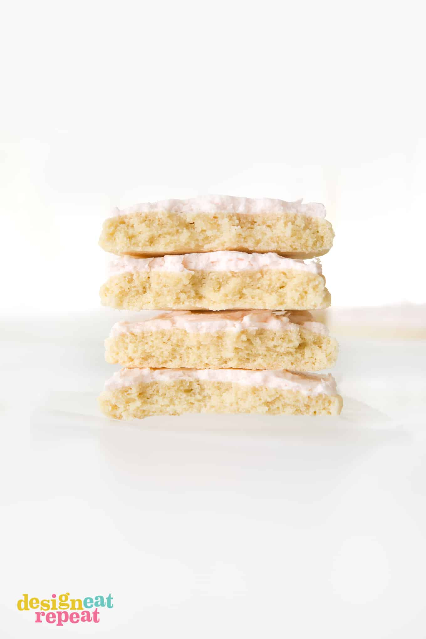 Stack of four large sugar cookies with pink frosting, cut in half.