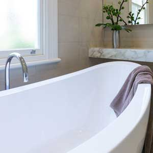 Porcelain bath with freestanding tap.
