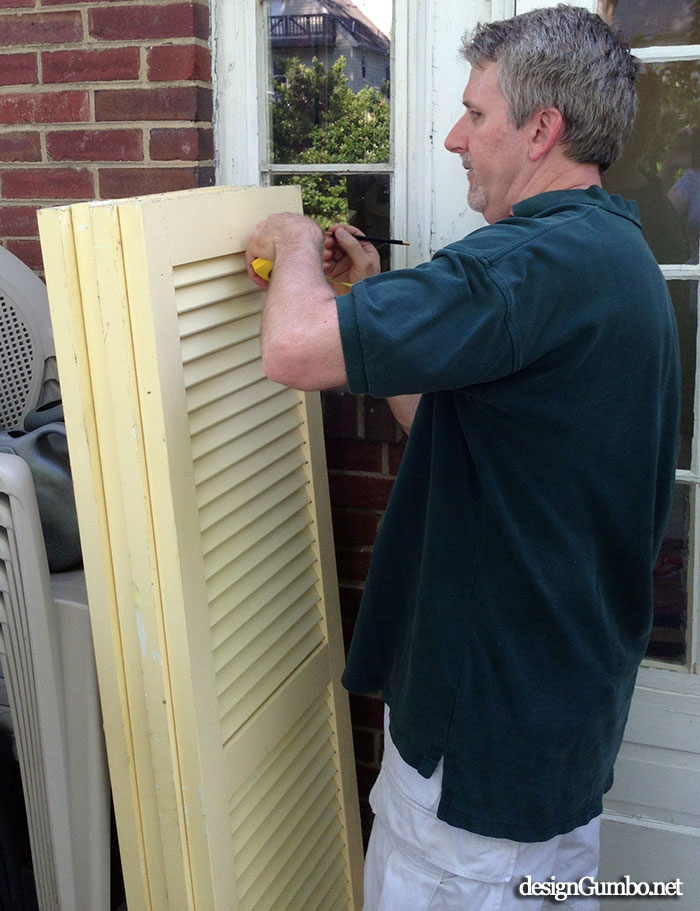 Measuring the shutters to hang on the brick wall