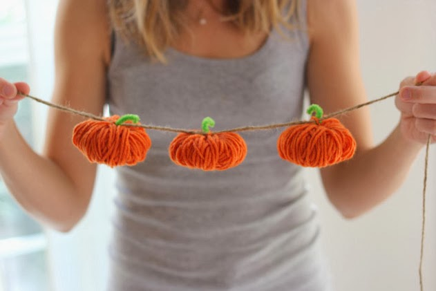 Hands holding a fall pumpkin garland