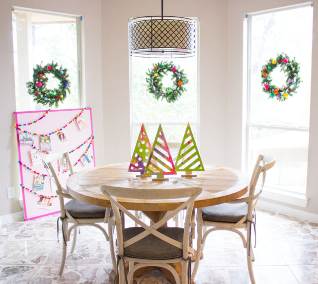 A colorful Christmas kitchen with pom-pom wreaths in the windows!