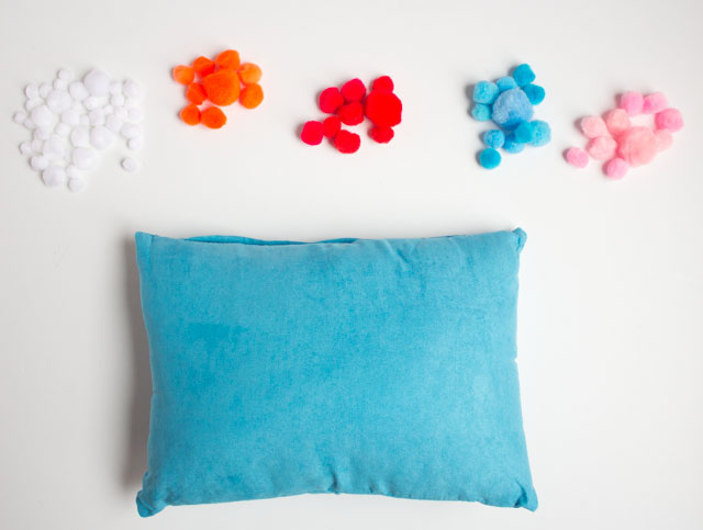 Decorate a pillow with pom-poms!