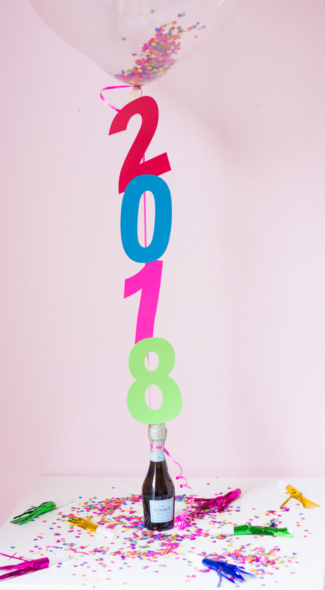 The perfect DIYt New Years Eve decoration - confetti filled number balloons with a champagne balloon weight!