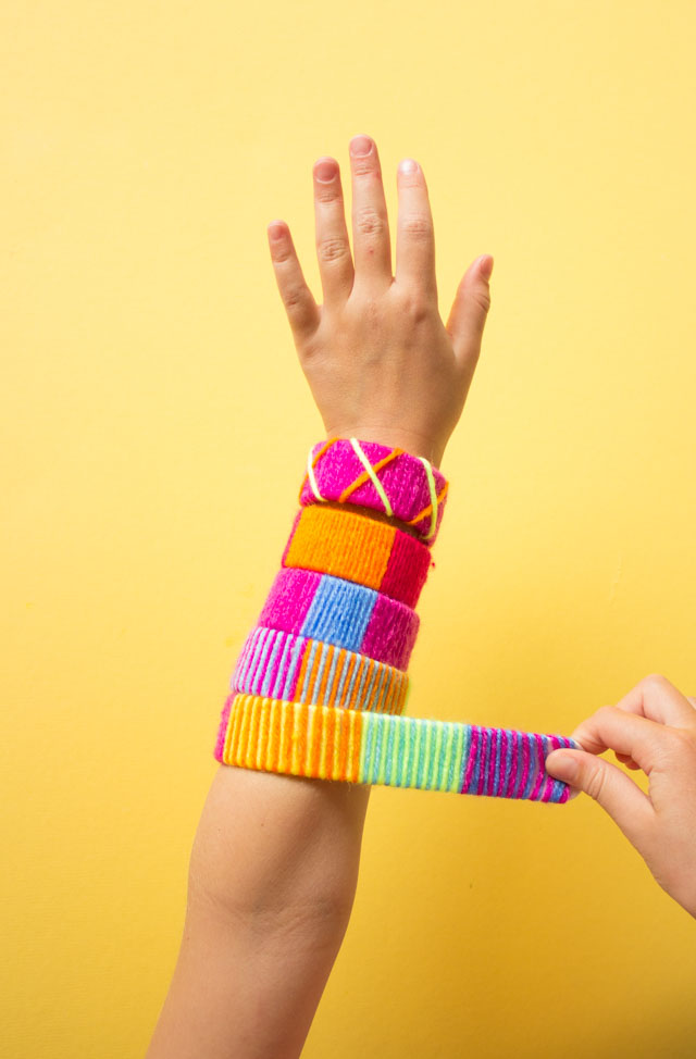 Make the coolest slap bracelets by wrapping them with yarn! #slapbracelets #kidscrafts #80scrafts #yarncrafts