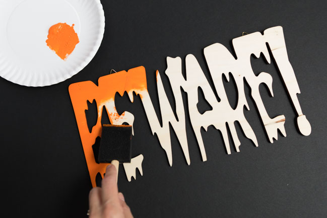 Painting wood Beware sign with orange paint
