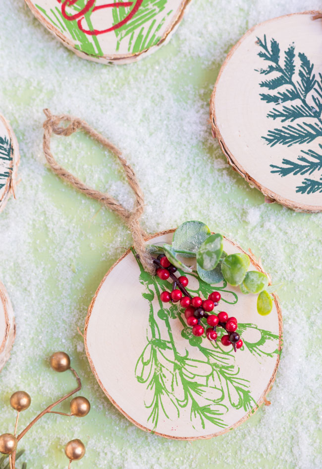 DIY wood slice ornaments with winter greenery