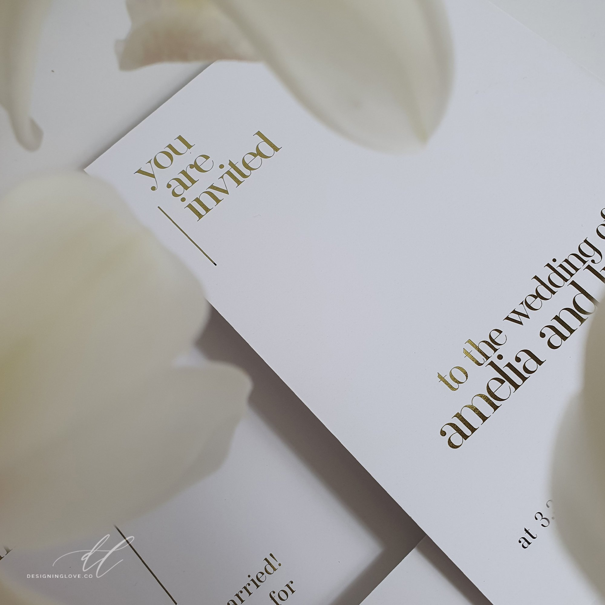 clean and simple wedding invitation with a top left aligned header you are invited. The couples names are in bold serif type in lower third of the card and time date and location details are in smaller type in the footer of the card in the foreground out of focus are white orchids
