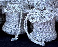 Close up of crochet perfume pouches with twisted drawstring, and slider bead