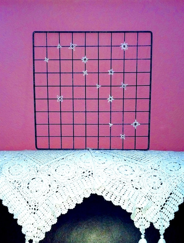 wire mesh panel decor with a freeform constellation of crochet stars