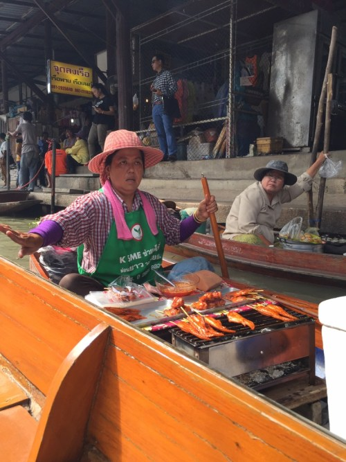 A lady in her boat selling her products.