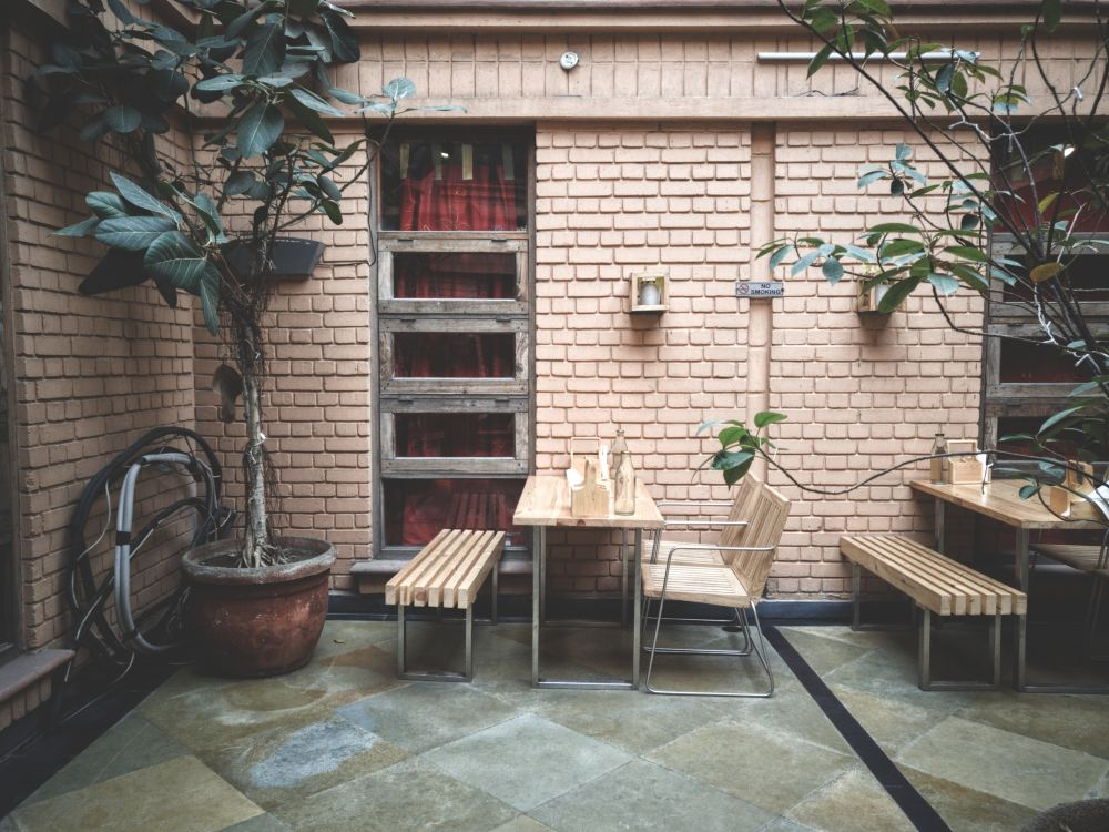 table and chair beside brick wall and green-leafed plant
