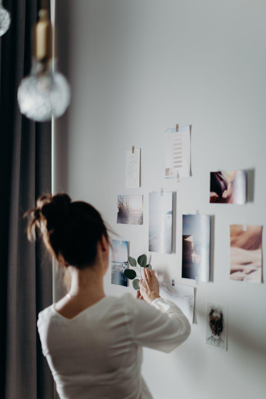 woman putting photo on wall