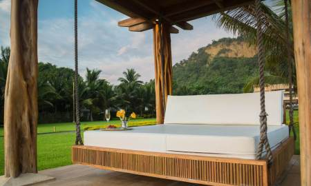 brown wooden framed with white mattress hanging bed surrounded by green grass