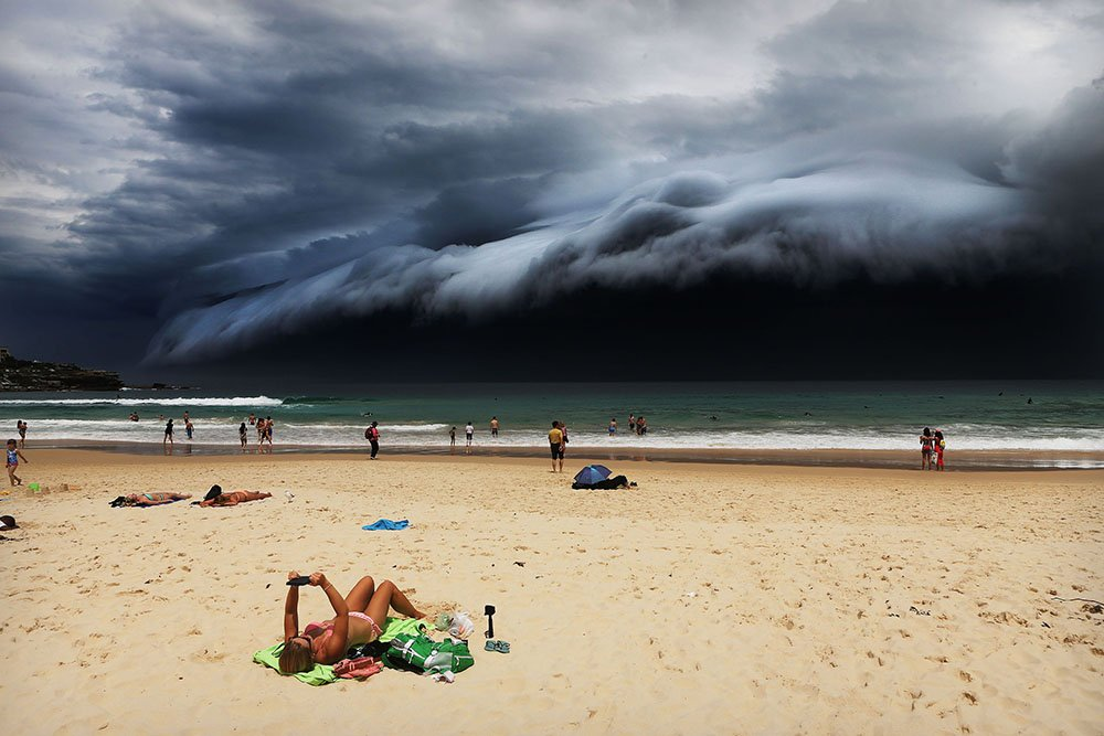 """Sunbather oblivious to the ominous shelf cloud approaching - on Bondi beach. A massive """"cloud tsunami"""" looms over Sydney in a spectacular weather event seen only a few times a year. The enormous shelf cloud rolled in from the sea, turning the sky almost black and bringing violent thunderstorms in its wake."""