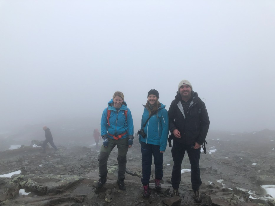 three people standing on top of bitihorn with the only view being fog