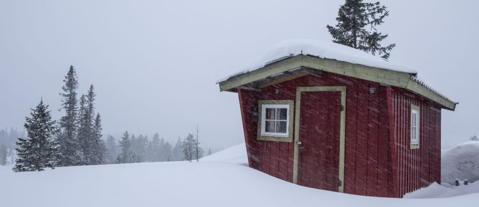 Small red cabin in the forest with snow