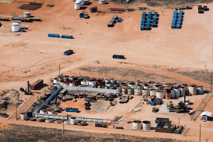 Aerial view of industrial site with dozens of open tanks of oilfield waste and barrels stacked up in the desert