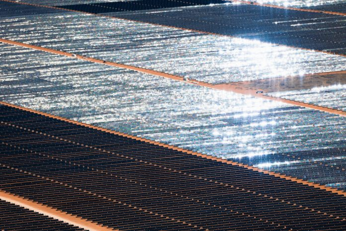Aerial view of endless rows of solar panels, some gleaming in the sunlight, in a red dirt desert.