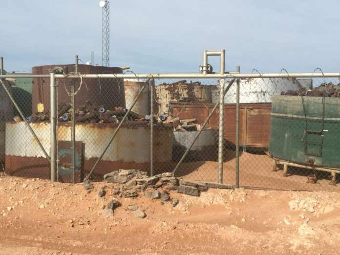Large rusty, white, and green tanks with rusted pipe sections sit behind a chainlink fence in the red-dirt desert.