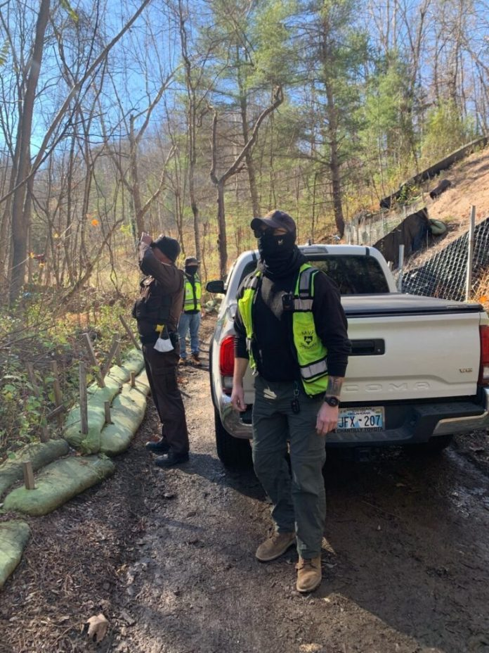 Three men wearing security clothing stand next to a white truck in woods in Virginia