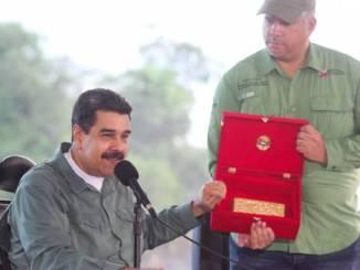 Fotografía cedida por prensa de Miraflores donde se observa al mandatario venezolano, Nicolás Maduro (i), quien muestra un lingote de oro, durante un acto de Gobierno el 5 de diciembre del 2017, en Bolívar (Venezuela).
