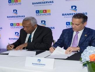 Magino Corporán, director del Consejo Nacional de Discapacidad (CONADIS), y Rienzi Pared Pérez, subadministrador de empresas subsidiarias de Banreservas, firman el acuerdo para facilitar transacciones a personas con discapacidad.