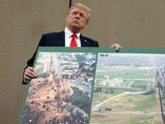 El presidente Donald Trump sostiene la imagen de un prototipo del muro fronterizo, en San Diego,