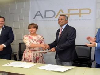 Los presidente ADAFP y Asonahores , muestran el documento que firmaron durante un encuentro. A ambos lados aparecen loa presidentes de la súper intendencia de pensiones y valores, Ramón contrera y Grabiel castro