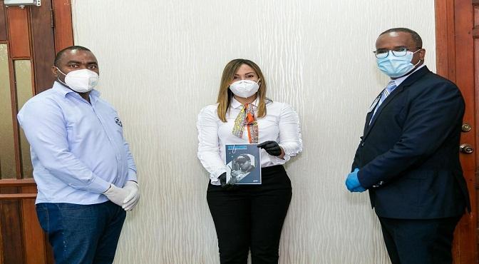 La doctora Mirna Font-Frías y el encargado de Seguridad y Transportación del SRSM, mayor de laFuerza Aérea Dominicana, Jonatan Corcino, reciben delcoronel Ramón Andújar, la Guía de Actuación de Seguridad Física para los Establecimientos de Salud de la Red Pública