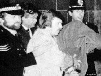 Peter William Sutcliffe, de 35 años, debajo de una manta (a la derecha), es conducido desde el Tribunal de Magistrados de Dewsbury por agentes de policía. (1981)